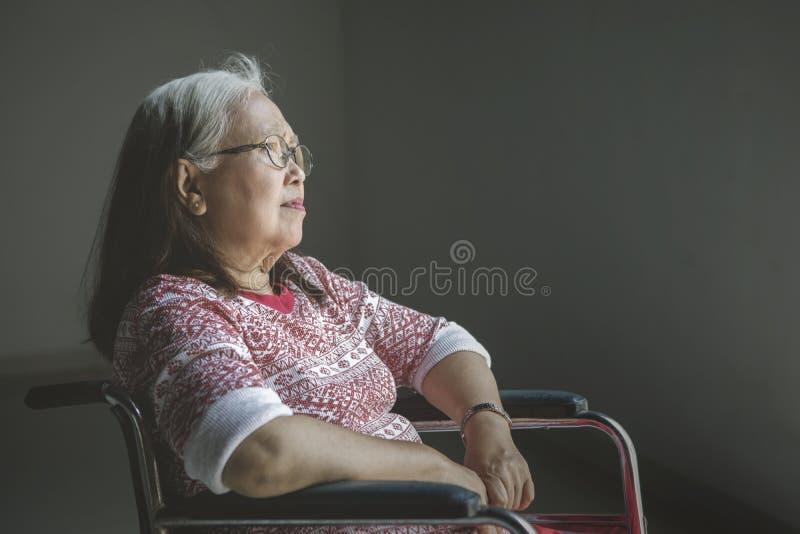Den höga kvinnan ser eftertänksam i en rullstol royaltyfria foton