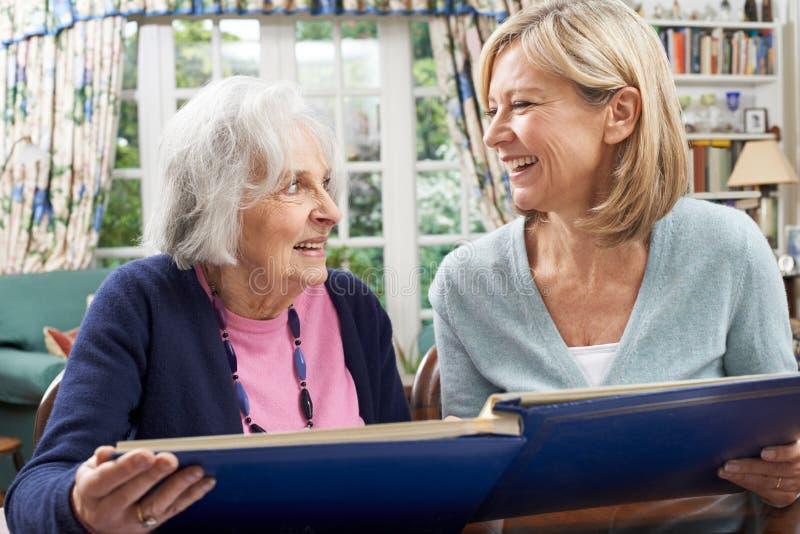 Den höga kvinnan ser fotoalbumet med den mogna kvinnliga grannen royaltyfria bilder