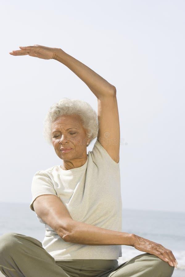 Den höga kvinnan sitter i yoga poserar royaltyfri bild