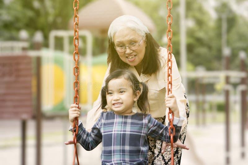 Den höga kvinnan skjuter hennes barnbarn på gungan fotografering för bildbyråer