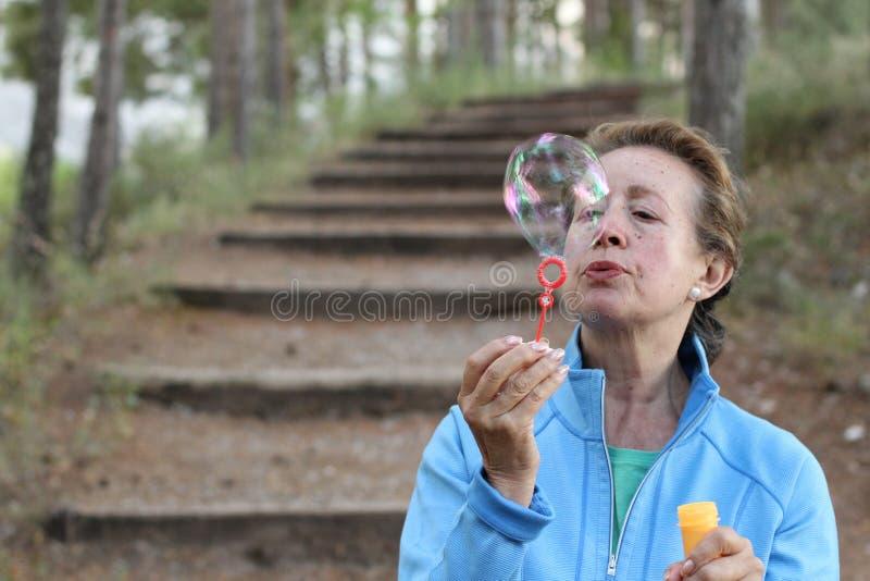 Den höga kvinnan som blåser såpbubblor i sommar, parkerar med kopieringsutrymme fotografering för bildbyråer
