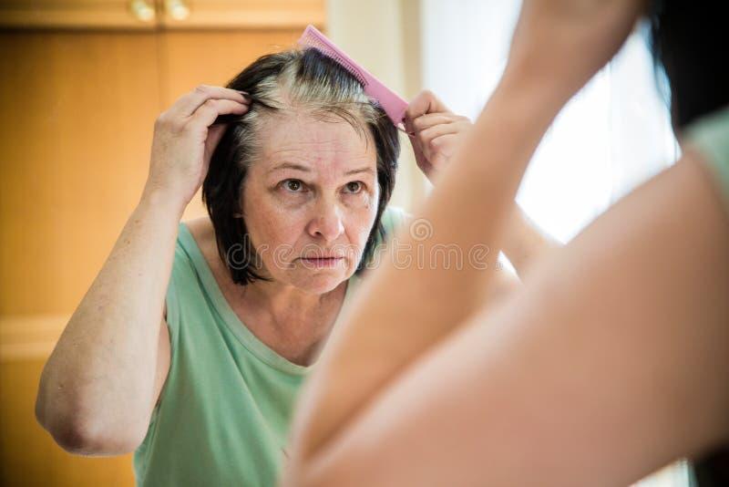 Den höga kvinnan som kontrollerar hennes gråa hår, rotar royaltyfri bild
