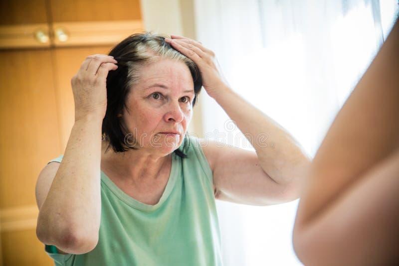 Den höga kvinnan som kontrollerar hennes gråa hår, rotar royaltyfria bilder