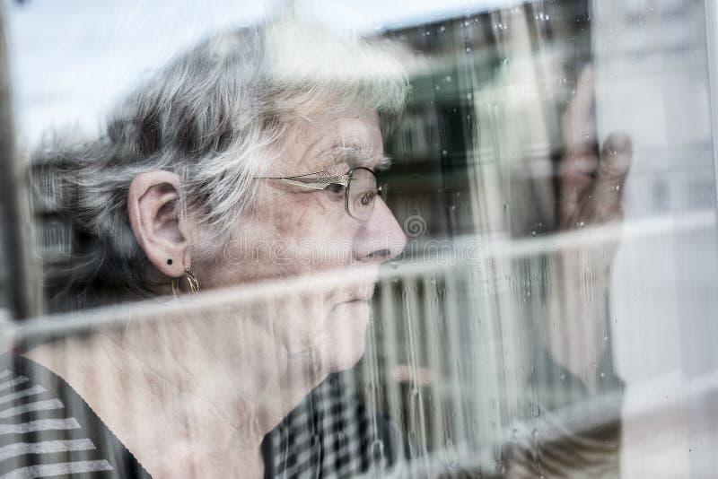 Den höga kvinnan som ut ser till och med ett fönster som, trycker ned arkivbild