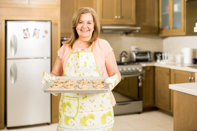 Den höga kvinnan som visar henne, bakade kakor arkivfoton