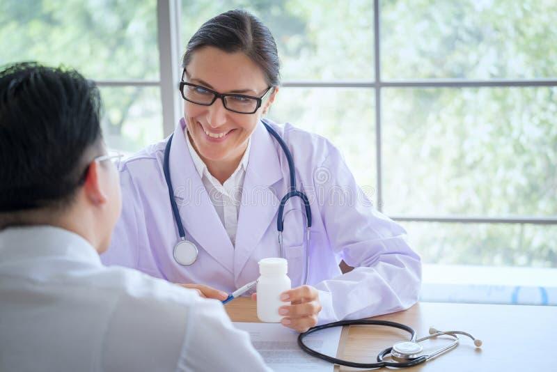 Den höga kvinnliga doktorn konsulterar ungt tålmodigt sammanträde på doktorn av arkivfoto