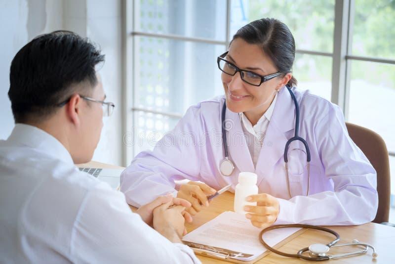 Den höga kvinnliga doktorn konsulterar ungt tålmodigt sammanträde på doktorn av royaltyfri fotografi