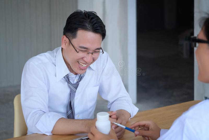 Den höga kvinnliga doktorn konsulterar ungt tålmodigt sammanträde på doktorn av arkivbild