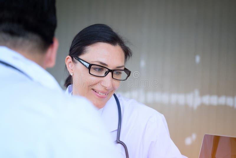 Den höga kvinnliga doktorn konsulterar ungt tålmodigt sammanträde på doktorn av royaltyfri bild