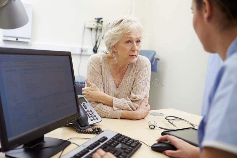 Den höga kvinnliga patienten har tidsbeställning med sjuksköterskan royaltyfri foto