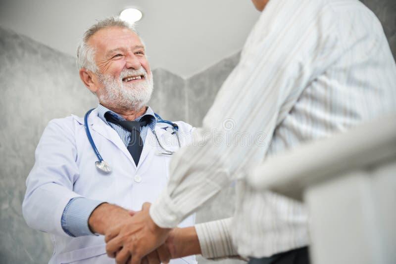 Den höga manliga doktorn är handshaking till den asiatiska manliga patienten royaltyfri foto