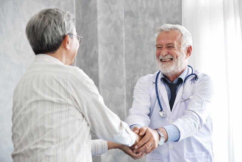 Den höga manliga doktorn är handshaking till den asiatiska manliga patienten royaltyfri fotografi