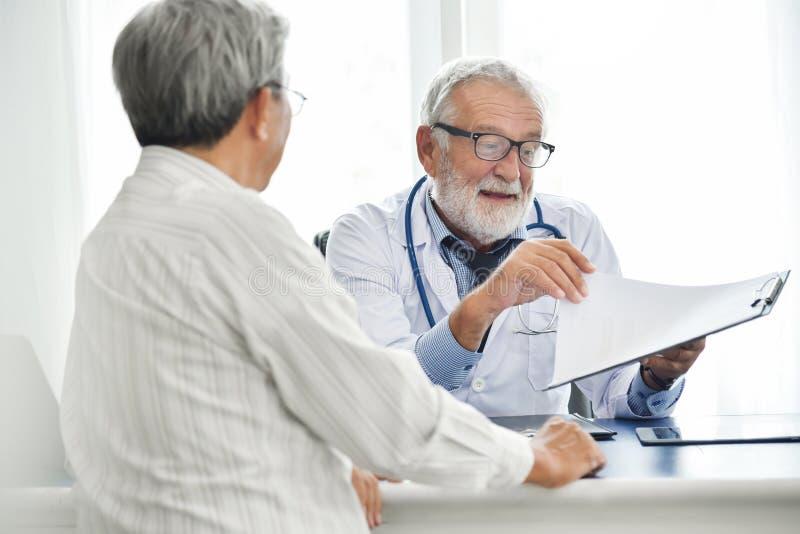 Den höga manliga doktorn diskuterar med den asiatiska manliga patienten fotografering för bildbyråer