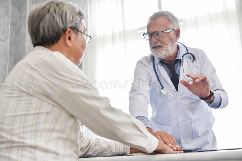 Den höga manliga doktorn diskuterar med den asiatiska manliga patienten royaltyfria bilder