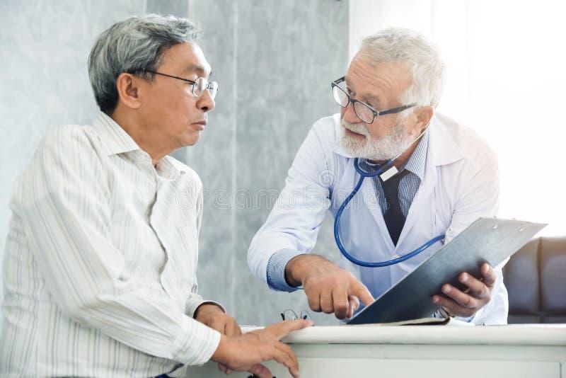 Den höga manliga doktorn diskuterar med den manliga patienten royaltyfri bild