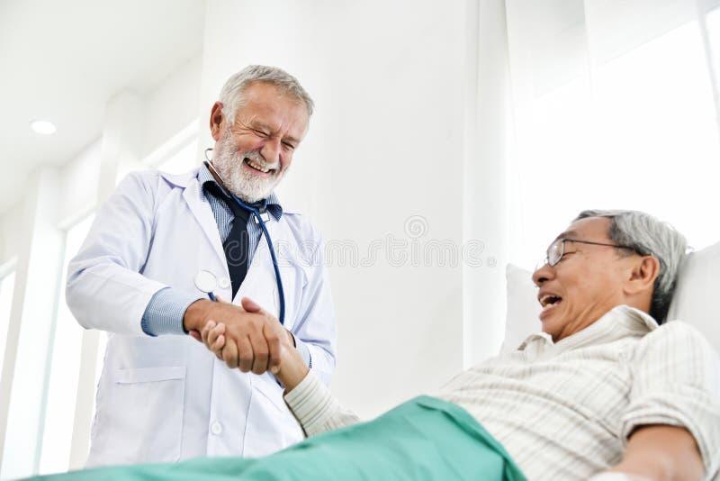 Den höga manliga doktorn talar med den asiatiska manliga patienten royaltyfria bilder