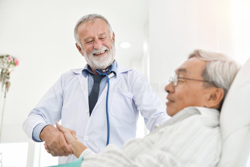 Den höga manliga doktorn talar med den asiatiska manliga patienten royaltyfri fotografi