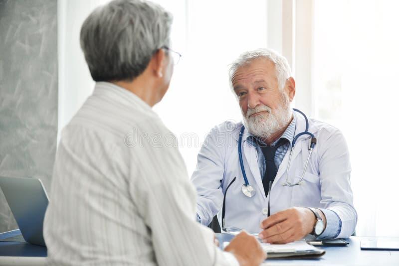 Den höga manliga doktorn talar med den asiatiska manliga patienten royaltyfri foto
