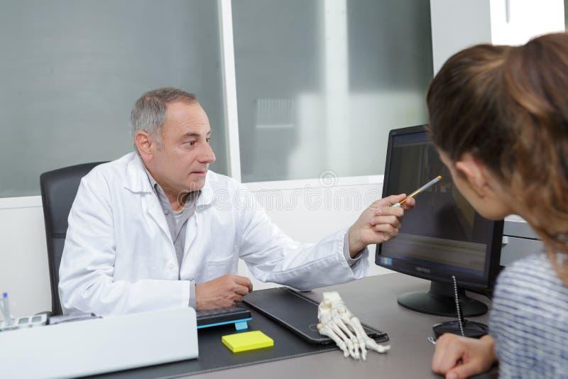 Den höga manliga doktorsvisningen resulterar till den kvinnliga patienten arkivbilder