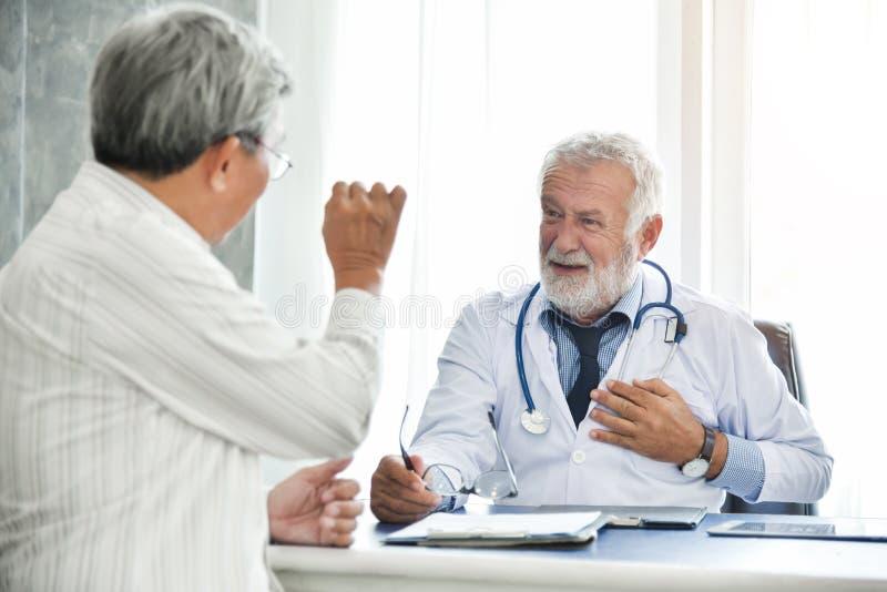 Den höga manliga manliga patienten för doktorn och för asiatet talar fotografering för bildbyråer