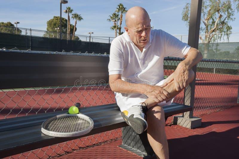 Den höga manliga tennisspelaren med benet smärtar sammanträde på bänk på domstolen royaltyfri bild