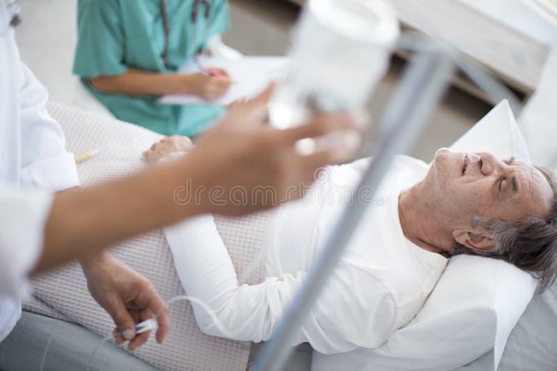 Den höga mannen är allvarligt dåligt i sjukhussäng royaltyfria foton