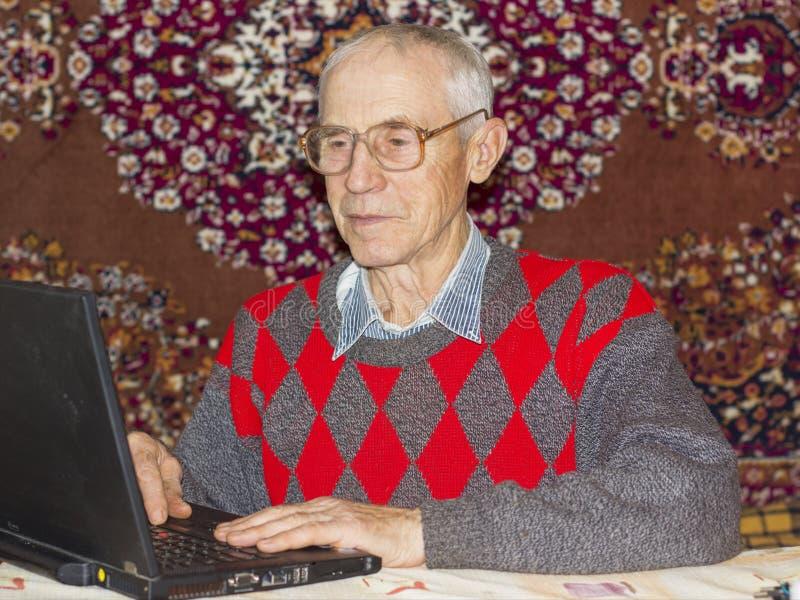 Den höga mannen arbetar hemma med bärbara datorn och glasögon royaltyfri fotografi
