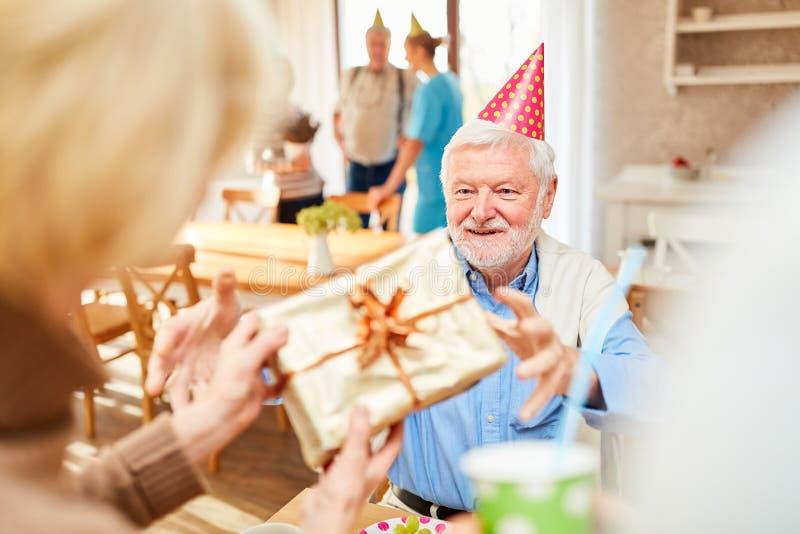 Den höga mannen ler lyckligt över en gåva royaltyfri foto