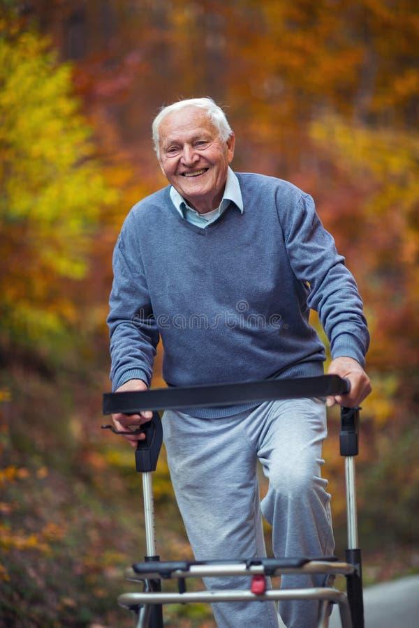 Den höga mannen med ett gå handikapp som tycker om en gå i en höst, parkerar fotografering för bildbyråer