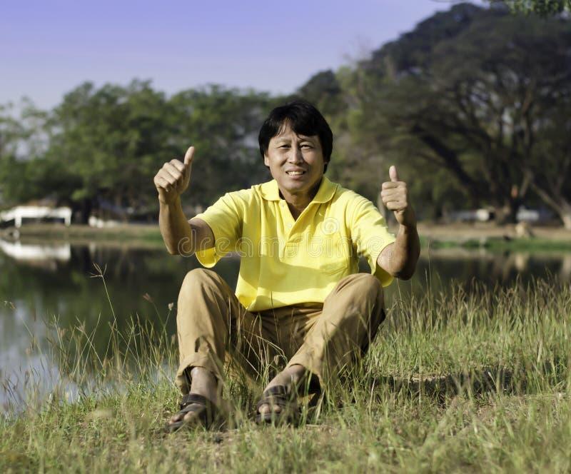 Den höga mannen med tummen upp mot en gräsplan parkerar royaltyfri fotografi