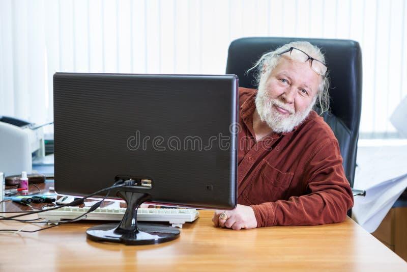 Den höga mannen ser ut bakifrån bildskärmen som sitter på kontorsskrivbordet, exponeringsglas på hans panna royaltyfria bilder