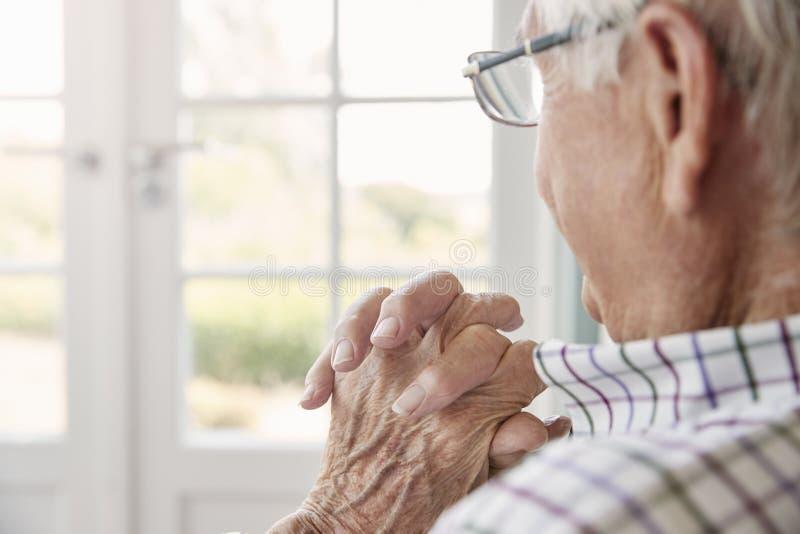 Den höga mannen sitter att se ut ur fönstret hemma, tätt upp arkivfoto