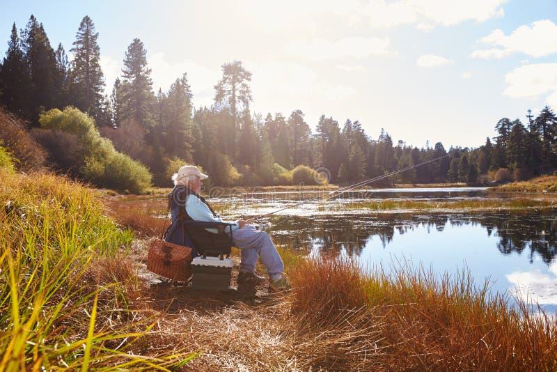 Den höga mannen sitter fiske, den rättframa sjön, Big Bear, Kalifornien royaltyfria foton