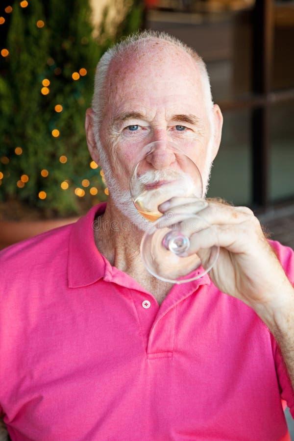Den höga mannen tycker om ett exponeringsglas av Wine royaltyfria foton