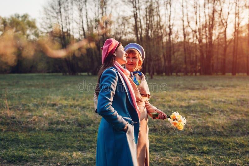 Den höga modern och hennes vuxna dottern som går i vår, parkerar Fostra dagbegreppet f?r ` s Familjev?rderingar royaltyfria bilder