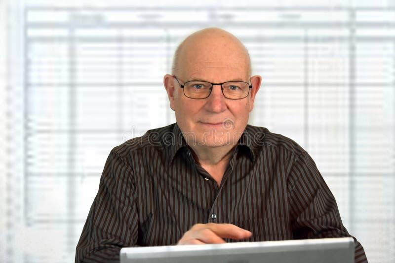 Den höga påklädden för framstickande arbetar tillfälligt i hans kontor arkivfoto