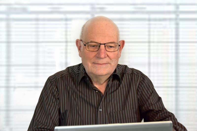 Den höga påklädden för framstickande arbetar tillfälligt i hans kontor arkivbilder