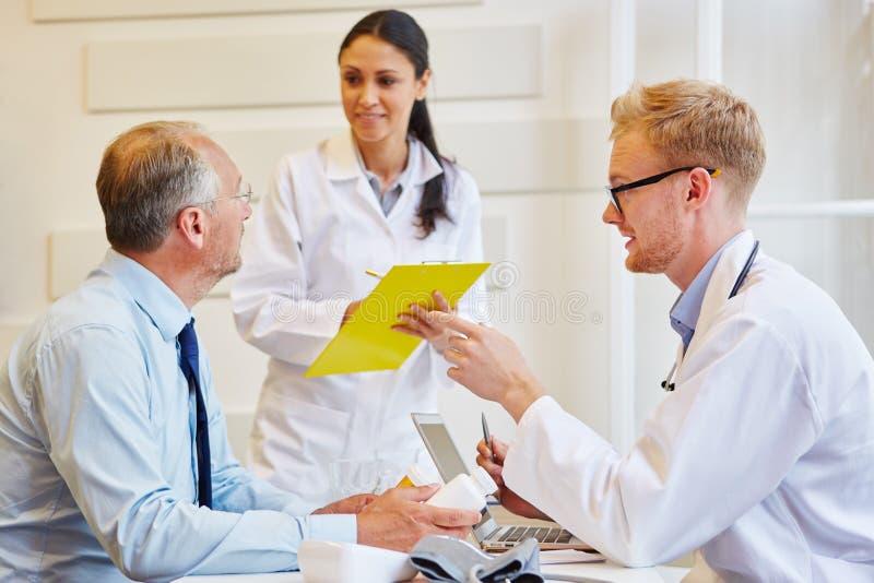 Den höga patienten mottar rådgivning från doktorer arkivfoto