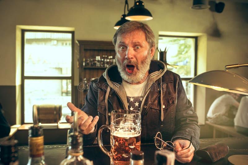 Den höga skäggiga mannen som dricker öl i bar arkivbilder