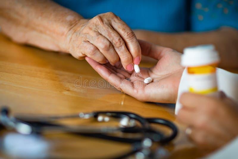 Den höga vuxna kvinnan som tar medicinpreventivpilleren från doktorer, gömma i handflatan royaltyfri bild