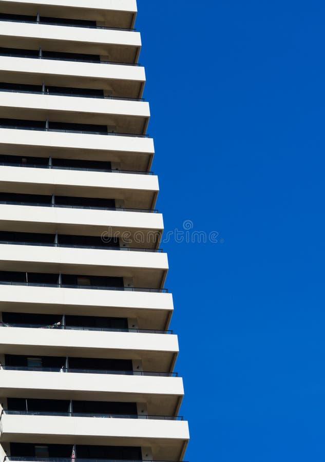 Den högväxta byggnaden för perspektivbalkong i vit med blå himmel arkivbild