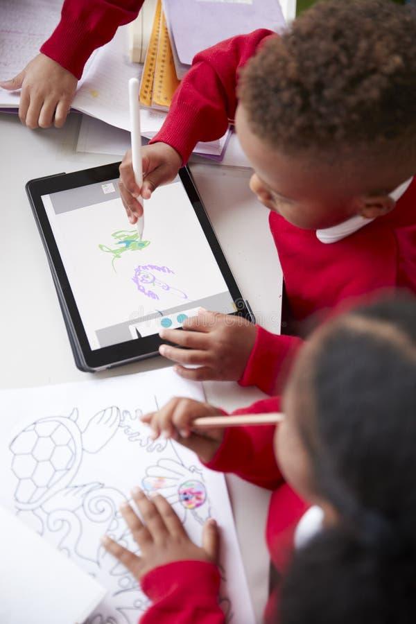Den höjde sikten av två dagisskolaungar som sitter på ett skrivbord i en klassrumteckning med en minnestavladator och nål, stänge arkivfoto