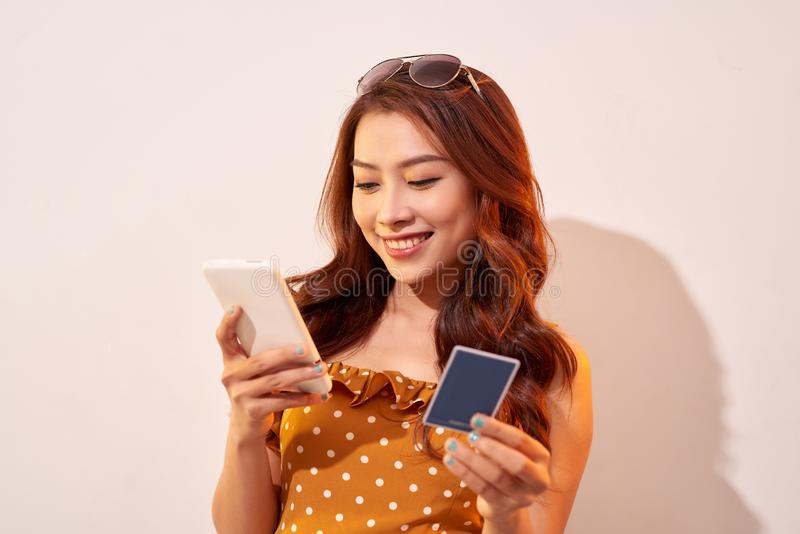 Den h?rliga asiatiska eleganskvinnlign tycker om online-shopping med begrepp f?r kreditkort- och smartphoneaff?rsid?er arkivbild