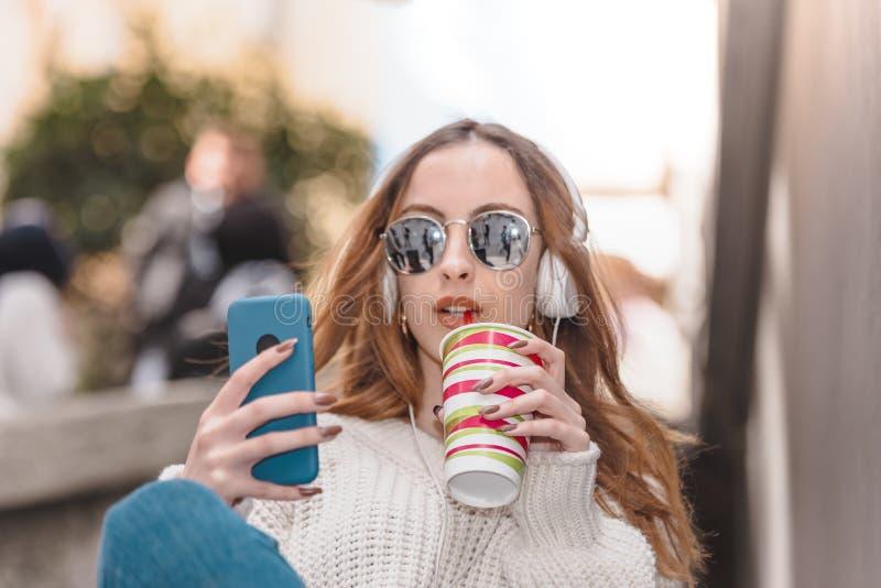 Den h?rliga attraktiva unga flickan anv?nder den smarta telefonen royaltyfria bilder