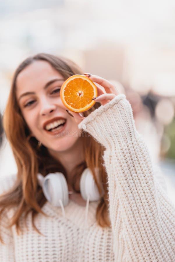 Den h?rliga attraktiva unga flickan rymmer halva av citrusfrukt arkivfoton