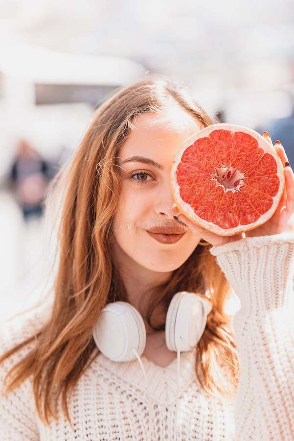 Den h?rliga attraktiva unga flickan rymmer halva av citrusfrukt royaltyfri fotografi