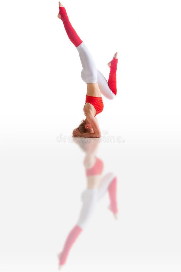 Den h?rliga b?jliga kvinnan som g?r yoga, poserar p? vit arkivbild