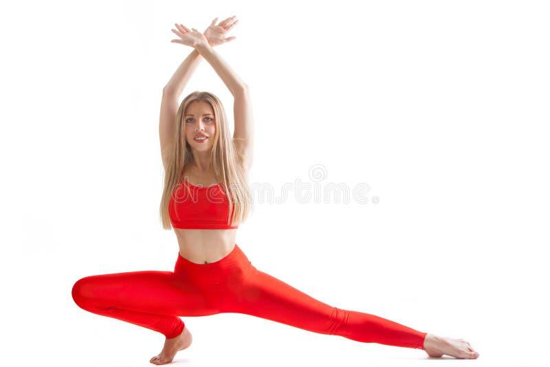 Den h?rliga b?jliga kvinnan som g?r yoga, poserar p? vit arkivbilder