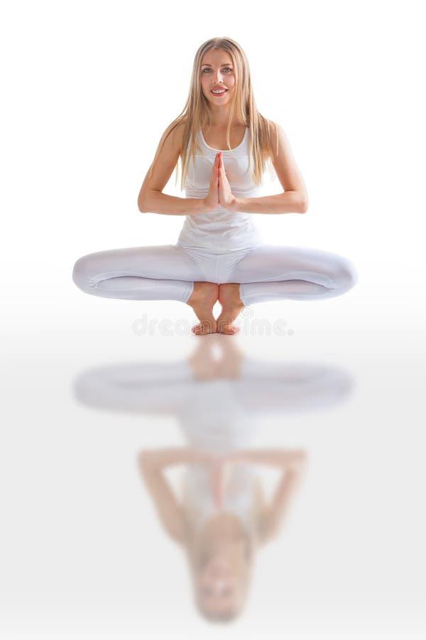 Den h?rliga b?jliga kvinnan som g?r yoga, poserar p? vit royaltyfri fotografi