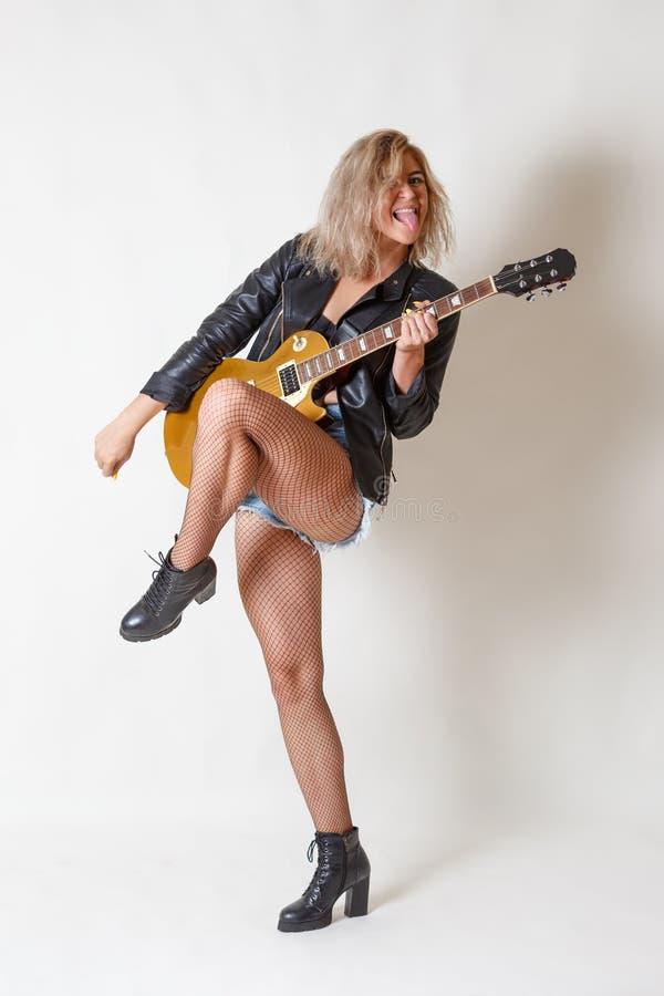 Den h?rliga blonda flickan spelar k?nslom?ssigt gitarren Showtunga Vit bakgrund arkivfoto